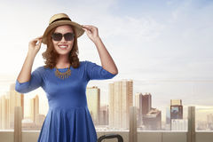 Beautiful asian woman with vintage hat standing in building terr. Ace against skyscraper background Stock Images