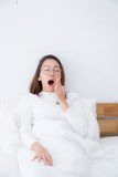 Beautiful asian woman waking up and yawn in bed in the bedroom Royalty Free Stock Photography