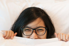 Beautiful asian woman wear eyeglasses waking up In bed. Royalty Free Stock Photo