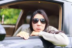 Asian woman protrudes from the window of the car. Beautiful asian woman wearing black glasses protrudes from the window of the car with smiling for the road trip Stock Photos