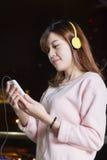 Beautiful Asian woman wearing headphones and holdi Royalty Free Stock Photos