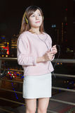 Beautiful Asian woman wearing headphones and holding cell phone Stock Photos