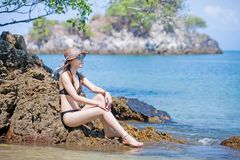 Asian woman wearing sunglasses in bikini relaxing on the beach. Beautiful Asian woman wearing sunglasses in bikini and beach hat relaxing on the beach stock images