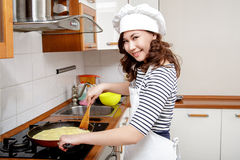 Beautiful Asian woman in white chef hat preparing an omelet in the kitchen. Royalty Free Stock Photography