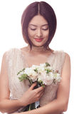 Beautiful asian woman in white dress with bouquet of flowers in hands Stock Images
