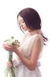 Beautiful asian woman in white dress with bouquet of flowers in hands Royalty Free Stock Image