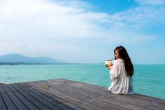 Woman on white dress sitting at the terrace drinking coconut juice with sea and blue sky background with feeling relaxed Royalty Free Stock Photos