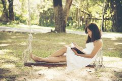 Beautiful asian woman in a white dress sitting on a wooden swing Stock Images
