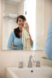 Beautiful asian woman wiping her face with towel, looking at mir Royalty Free Stock Photography
