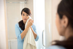 Beautiful asian woman wiping her face with towel, looking at mir Stock Photo