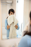 Beautiful asian woman wiping her face with towel, looking at mir Stock Image