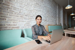 Beautiful Asian  woman working on net-book during morning breakfast in cafe bar. Young charming female freelancer using laptop computer for distance job while Royalty Free Stock Photography