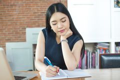 Beautiful Asian woman writing a notebook on table with laptop as Royalty Free Stock Photography