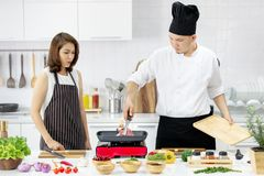 Beautiful Asian woman in black apron feel wondering while seeing stock images