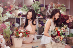 Beautiful asian women florists with bouquet of flowers in flower store Royalty Free Stock Photos