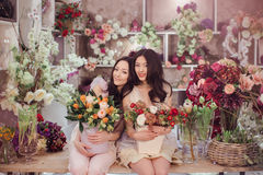Beautiful asian women florists with bouquet of flowers in flower store Stock Photos