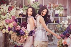 Beautiful asian women florists happy working in flower store with a lot of spring flowers. Beautiful asian florist girls holding bouquet and basket of flowers royalty free stock photography