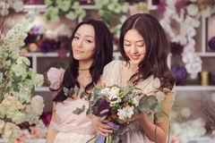 Beautiful asian women florists happy working in flower store with a lot of spring flowers. Beautiful asian florist girls making bouquet of flowers for sale royalty free stock images