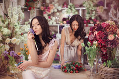 Beautiful asian women florists happy working in flower store with a lot of spring flowers Royalty Free Stock Image