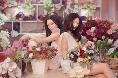 Beautiful asian women florists working in flower store with a lot of spring flowers Royalty Free Stock Photography