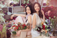 Beautiful asian women florists working in flower store with a lot of spring flowers Stock Images