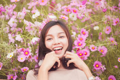 Beautiful asian women smiling in pink cosmos flower field Stock Image