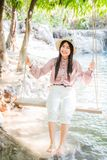 Beautiful Asian women, Thai people, wearing pink casual clothes with a refreshing and smiling face are sitting on the swings. Beautiful Asian women, Thai people stock photos