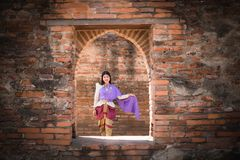 Beautiful Asian women, Thai people wearing Thai clothes, standing on the old wall. Beautiful Asian women, Thai people wearing Thai clothes, standing on the old stock images