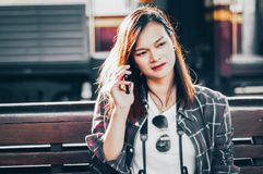 Beautiful Asian women traveler, Sit and talk smartphone happily on wooden benches in train station background, Concepts Travel royalty free stock images
