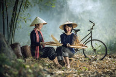 Beautiful Asian women winnowing grain with a happy smile. royalty free stock photography