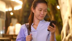 Beautiful Asian young business woman using application on smart phone texting chat with friend at outdoor with smiling face stock footage