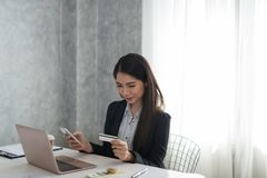 Beautiful asian young businesswoman holding phone and credit car. D  buying on line. Online shopping, technology concept Royalty Free Stock Image
