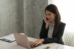 Beautiful asian young businesswoman working on laptop while be s. Mile phone in her workstation at desk with bright window in background Stock Photos