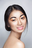 Beautiful Asian young tender woman smiles and looks in camera Stock Photos