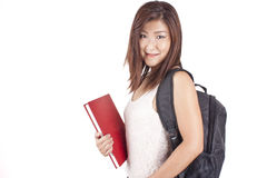 Beautiful Asian young woman with backpack holding red book Stock Photo