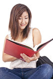 Beautiful Asian young woman with backpack reading red book= Stock Images