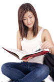 Beautiful Asian young woman with backpack reading red book Royalty Free Stock Photos