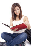 Beautiful Asian young woman with backpack reading red book Royalty Free Stock Photography