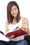 Beautiful Asian young woman with backpack reading red book Royalty Free Stock Image