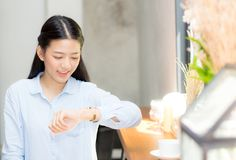 Beautiful asian young woman look at watch waiting for friend or someone. Stock Photo