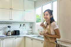 Beautiful asian young woman is looking to cooking in kitchen at. Home,Woman is eating salad Royalty Free Stock Images