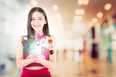 Beautiful asian young woman in red dress holding shopping cart royalty free stock image