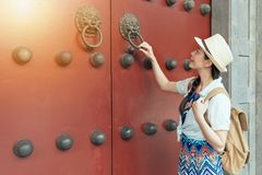 Woman play knock wooden red door. Beautiful asian young woman relaxing on summer holiday by ancient traditional and play knock wooden red door in Chinese temple stock photos