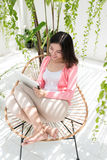 Beautiful asian young woman relaxing and using digital tablet at. Home Royalty Free Stock Images