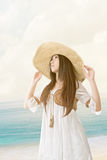 Beautiful asian young woman with seascape backgrou. Outdoor portrait of a beautiful asian young woman wearing knitted hat at the beach with seascape background stock images