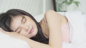 Beautiful asian young woman sleeping lying in bed with happy and smile in the bedroom