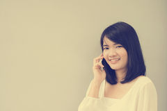 Beautiful asian young woman talking on Mobile Phone over concrete wall. Stock Photo