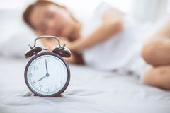 Beautiful asian young woman turn off alarm clock in good morning, wake up for sleep with closeup foreground alarm clock. Beautiful asian young woman turn off Royalty Free Stock Image