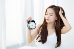 Beautiful asian young woman wake up in morning annoyed alarm clock holding hand Royalty Free Stock Photo
