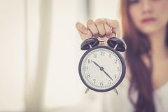 Beautiful asian young woman wake up in morning annoyed alarm clock holding hand Royalty Free Stock Photos